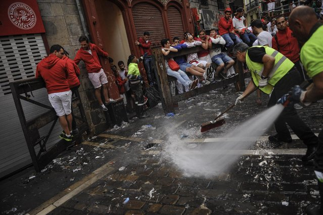 Workers clean Estafeta corner prior to start Conde de la Maza fighting bulls during the sixth running of the bulls, at the San Fermin Festival, in Pamplona, Spain, Sunday, July 12, 2015. Revelers from around the world arrive to Pamplona every year to take part in some of the eight days of the running of the bulls. (Photo by Alvaro Barrientos/AP Photo)
