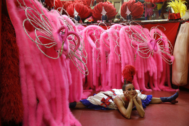 """Axelle streches as she warms up before performing the French Cancan at the """"Feerie"""" review at the Moulin Rouge, in Paris, France, September 19, 2019. (Photo by Philippe Wojazer/Reuters)"""