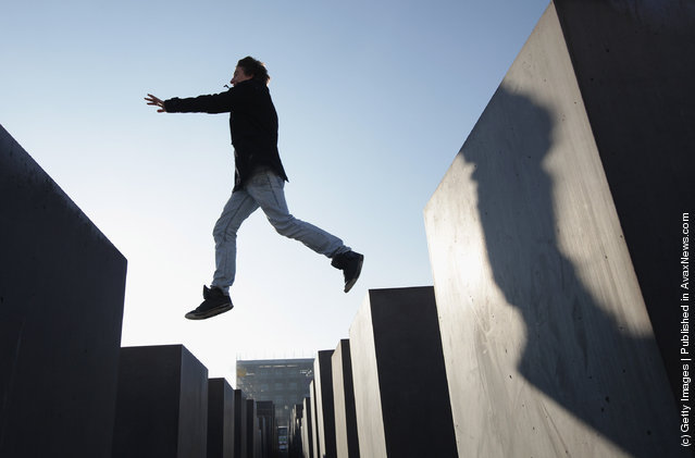 Visitors walk among stellae at the Memorial to the Murdered Jews of Europe, also called the Holocaust Memorial