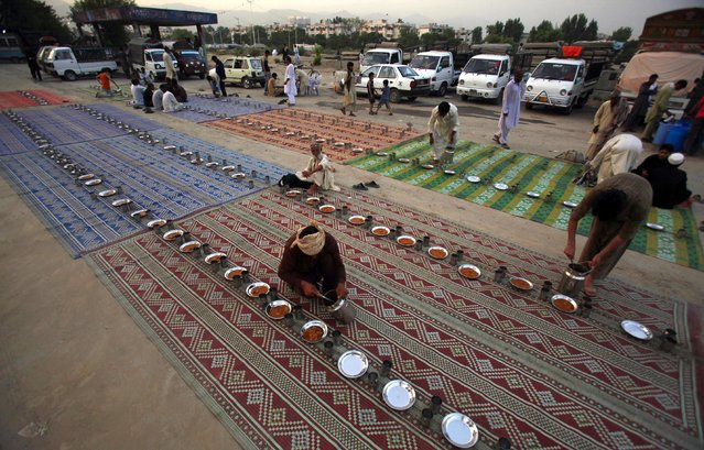 Pakistani volunteers arrange plates for devotees to break their Ramadan fast in Islamabad, Pakistan, Sunday, July 5, 2015. Muslims across the world are observing the holy fasting month of Ramadan, when they refrain from eating, drinking and smoking from dawn to dusk. (Photo by Anjum Naveed/AP Photo)