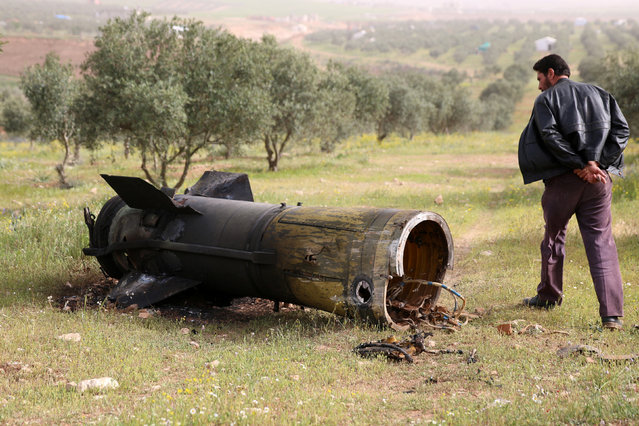 A man inspects a piece of a rocket that landed south of Daraa Al-Balad, Syria, April 5, 2017. (Photo by Alaa Al-Faqir/Reuters)