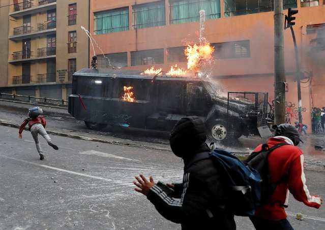 A police vehicle burns during a protest against Ecuador's President Lenin Moreno's austerity measures in Quito, Ecuador, October 7, 2019. Ecuadorean protesters have clashed with security forces and blocked highways for five days to demonstrate against government austerity measures, including the end of four-decade-old fuel subsidies. (Photo by Carlos Garcia Rawlins/Reuters)