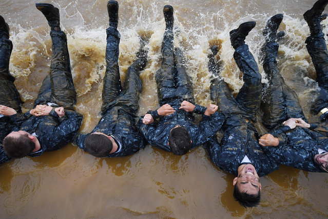 "United States Naval Academy plebe, John Caniban, bottom right center, grimaces as he takes part in the ""Wet and Sandy"" portion of Sea Trials at the United States Naval Academy on Tuesday May 17, 2016 in Annapolis, MD. (Photo by Matt McClain/The Washington Post)"