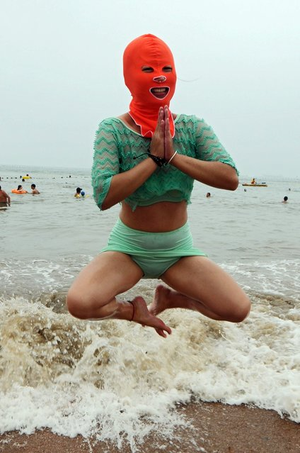 A swimmer wearing a hood known as facekini plays on the beach in Qingdao, east China's Shandong province, China, 16 July 2015. (Photo by Wang Haibin/EPA)