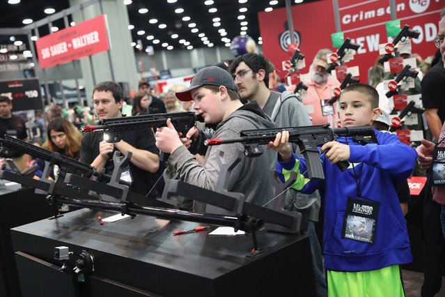 Gun enthusiasts try out the Crimson Trace laser sighting systems at the NRA Annual Meetings & Exhibits on May 21, 2016 in Louisville, Kentucky. About 80,000 visitors are expected to attend the three-day event. (Photo by Scott Olson/Getty Images)