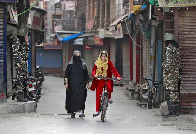 A Kashmir girl rides her bike past Indian security force personnel standing guard in front closed shops in a street in Srinagar, October 30, 2019. (Photo by Danish Ismail/Reuters)