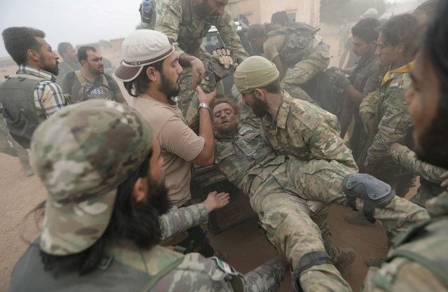 Turkey-backed Syrian rebel fighters assist their injured fellow fighter near the border town of Tal Abyad, Syria, October 24, 2019. (Photo by Khalil Ashawi/Reuters)