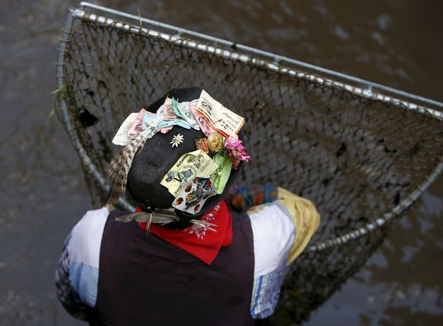 A fisherman takes a break after catching trouts in a small river during the Fischertag (Fisherman's Day) in downtown Memmingen, southern Germany, July 25, 2015. (Photo by Michaela Rehle/Reuters)