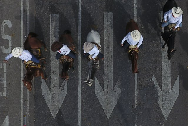 Men ride horses down Paseo de la Reforma during a parade marking the 109th anniversary of the start of the Mexican Revolution, in Mexico City, Wednesday, November 20, 2019. More than 1,000 participants dressed in period clothing rode through the streets of the capital after reenacting scenes from the revolution in the city's main square. (Photo by Rebecca Blackwell/AP Photo)