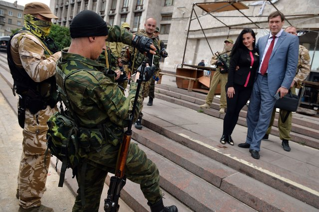 "A guard of the Vostok Battalion takes a picture of Ukrainian MP and withdrew candidate in the 2014 Ukrainian presidential election, Oleg Tsarev (R), posing outside the self-proclaimed ""Donetsk People's Republic"" headquarters in Donetsk, on June 12, 2014. (Photo by Daniel Mihailescu/AFP Photo)"