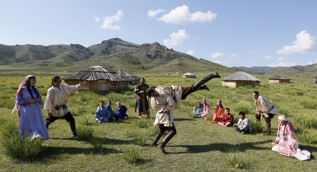 Members of national folklore and ethnographic groups and employees of a museum-reserve participate in the reconstruction of daily life and traditional holidays celebrated by indigenous population of the Republic of Khakassia during a demonstration for visitors outside Kazanovka village, southwest of the city of Abakan, Russia, July 24, 2015. (Photo by Ilya Naymushin/Reuters)