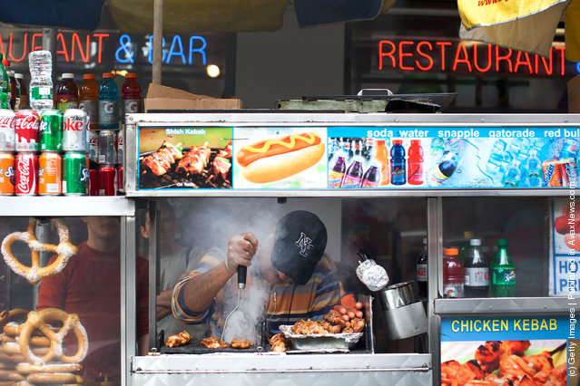 A food cart vendor cooks food in Times Square on March 23, 2012 in New York City