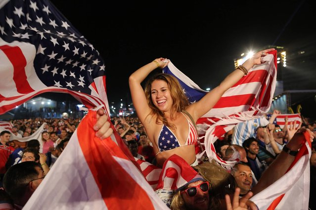 Fans of the U.S. national soccer team celebrate their team's victory during a live broadcast of the soccer World Cup match between the Unites States and Ghana, inside the FIFA Fan Fest area on Copacabana beach, Rio de Janeiro, Brazil, Monday, June 16, 2014. Clint Dempsey scored in the first minute and rookie substitute John Brooks scored a late game winner as the U.S. defeated Ghana 2-1 in the World Cup opener for both. (Photo by Leo Correa/AP Photo)