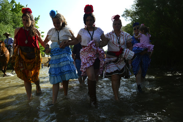 Pilgrims lift up their dresses as they cross the Quema river during the annual El Rocio pilgrimage in Villamanrique, near Sevilla on June 1, 2017. (Photo by Cristina Quicler/AFP Photo)