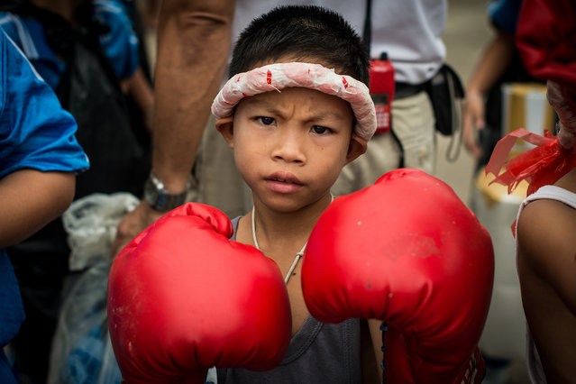 """""""Muay Thai Boy"""". This little Thai boy gave me an unexpected """"tough"""" look as soon as I readied my camera for this shot. He was dressed up for the village Sport Day in Pa Sang, Lamphun, where various schools annually come together to compete in athletic events for one day. There is a sense of strength and endurance that is instilled so deep in the hearts of the Thai people, and for a mere second, I could see it blooming in his eyes. Photo location: Lamphun, Thailand. (Photo and caption by Lauren Moffett/National Geographic Photo Contest)"""