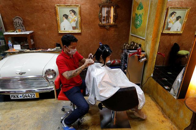 A woman get a haircut as a picture of Thailand's King Bhumibol Adulyadej having a haircut hangs on a wall at a beauty salon in Bangkok, Thailand, June 3, 2016. (Photo by Jorge Silva/Reuters)