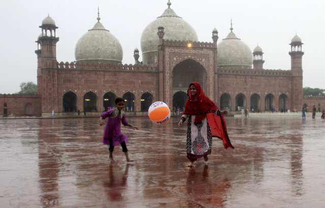 Pakistani children play in the rain outside the historical Badshahi mosque in Lahore, Pakistan, Friday, July 24, 2015. Pakistani authorities say flash floods, triggered by monsoon rains, have killed 12 more people across the country, bringing the overall death toll since early last week to 15, as rescuers struggle to move those stranded to safer places. (Photo by K. M. Chaudary/AP Photo)