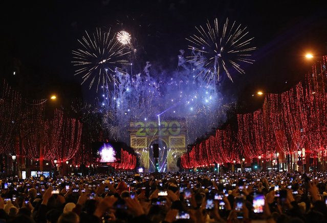 Revellers photograph fireworks over the Arc de Triomphe as they celebrate the New Year on the Champs Elysees, in Paris, France, Wednesday, January 1, 2020. (Photo by Christophe Ena/AP Photo)