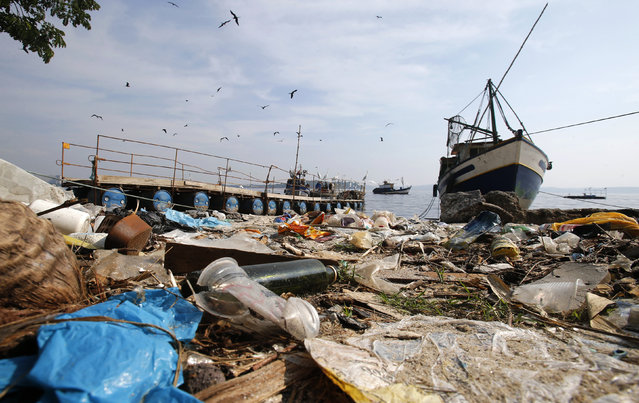 Garbage is seen near a fishing boat on Fundao beach in the Guanabara Bay in Rio de Janeiro March 13, 2014. (Photo by Sergio Moraes/Reuters)