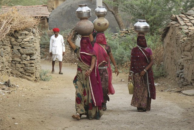 Women carry pitchers filled with drinking water in Devmali village in the desert state of Rajasthan, India, June 16, 2016. (Photo by Himanshu Sharma/Reuters)
