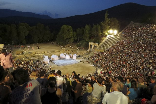"""Spectators are seen before a performance of Aristophanes' 2,400-year-old play """"Ecclesiazusae"""" (The Assembly Women) at the ancient Greek amphitheatre of Epidaurus, southern Greece August 1, 2015. While cash-strapped Greeks forgo the cinema and other luxuries, theatre ticket sales are booming – even if theatres struggle to cover their costs and actors often go unpaid. (Photo by Lefteris Karagiannopoulos/Reuters)"""