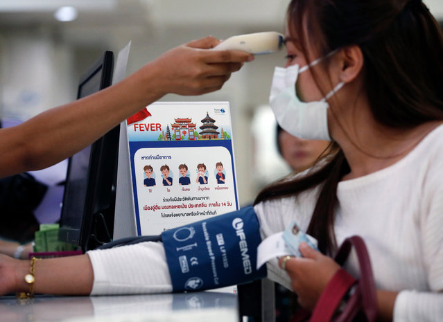A nurse checks a patient's body temperature next to a campaign poster alerting on the coronavirus at a hospital in Bangkok, Thailand, 22 January 2020. The SARS-like coronavirus was detected in three Chinese tourists as well as a 73-year-old Thai woman who was infected after traveling to Wuhan, China. China confirmed 440 cases of Wuhan pneumonia with nine deaths, according to the National Health Commission on a press conference. The respiratory virus was first detected in Wuhan and can be passed between humans. So far it has spread to the USA, Thailand, South Korea, Japan and Taiwan. (Photo by Rungroj Yongrit/EPA/EFE)