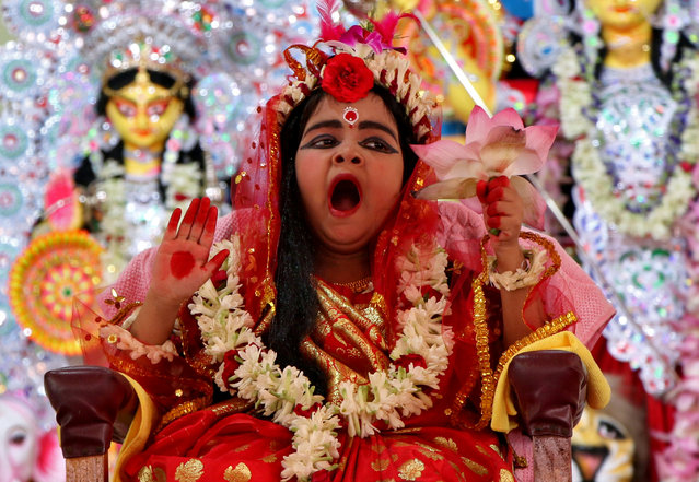 Nidhi Bhattacharjee, 5, dressed as a Kumari, yawns as she is worshipped by Hindu priests (unseen) as part of a ritual during the Durga Puja festival celebrations in Agartala, India, October 6, 2019. (Photo by Jayanta Dey/Reuters)