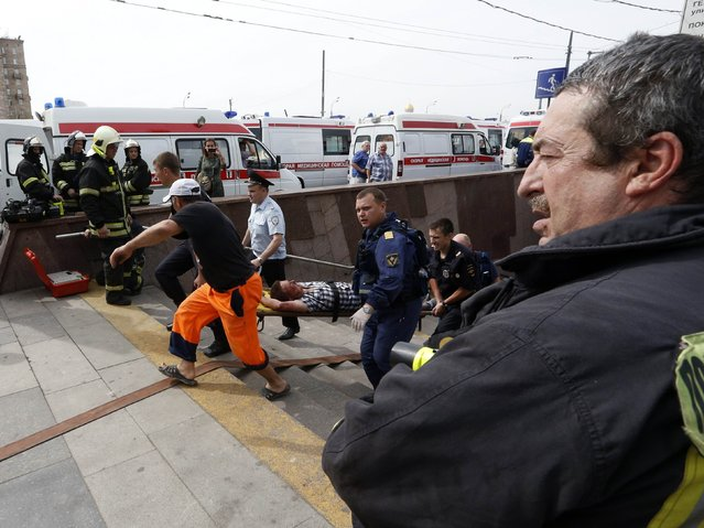 Members of the emergency services carry an injured passenger outside a metro station following an accident on the subway in Moscow July 15, 2014. (Photo by Sergei Karpukhin/Reuters)