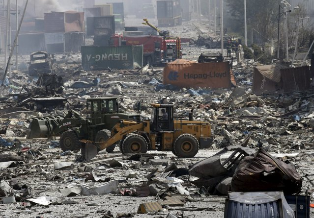Excavators work near the site of the explosions at the Binhai new district, Tianjin, August 13, 2015. (Photo by Jason Lee/Reuters)