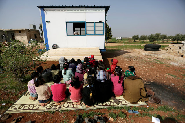 Children watch as volunteer teachers perform a puppet show inside a mobile educational caravan for children who do not have access to schools on the outskirts of the Syrian rebel-held town of Saraqib, Idlib province March 10, 2016. (Photo by Khalil Ashawi/Reuters)