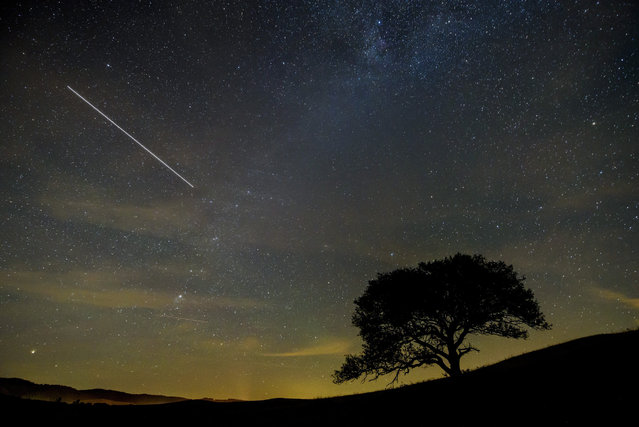 In this picture taken with a long time exposure the International Space Station (ISS) makes a line across the night sky above Kazar, 106 kms northeast of Budapest, Hungary, 27 July 2017. (Photo by Peter Komka/EPA)