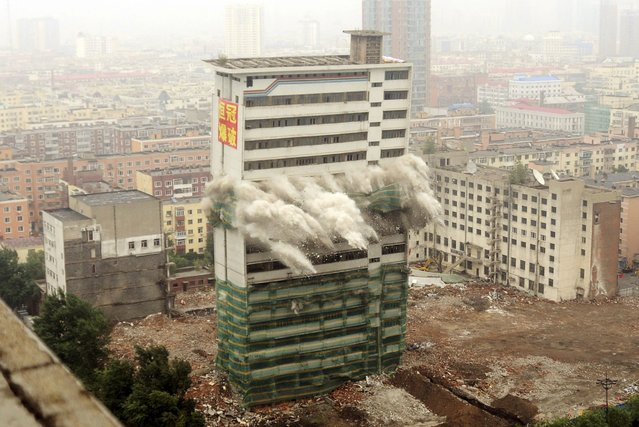 The former Heilongjiang TV station headquarters collapses as it is demolished by explosives to make way for the city's new administrative service centre in Harbin, Heilongjiang province, July 20, 2014. (Photo by Reuters/China Daily)