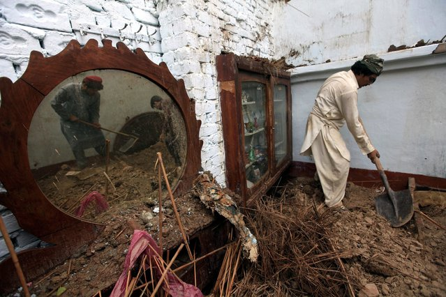 A picture made available on 16 June 2016 shows local residents removing debris after the roof of a house collapsed during heavy rains in Peshawar, Pakistan, 15 June 2016. At least two people died when a roof of a house collapsed in Peshawar while more than 30 injured across the provincial capiital in rain related incidents. (Photo by Arshad Arbab/EPA)