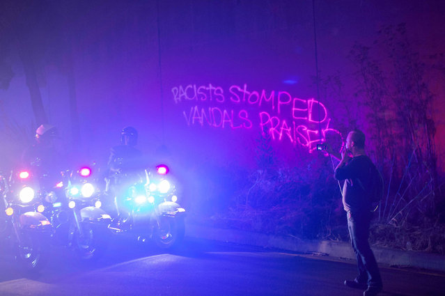 Graffiti on the wall is reflected in the police lights as protesters march down an onramp after blocking Interstate 580 to rally against racism in Oakland, California on August 12, 2017. Protesters marched on the streets of Oakland in response to a series of violent clashes that erupted at a white-nationalist rally in Charlottesville, Virginia earlier in the day that left at least one dead and dozens injured. (Photo by Josh Edelson/AFP Photo)