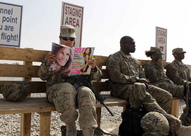 U.S. Army soldier SSG Norma Gonzales of 426 Civil Affairs Battalion reads a magazine next to fellow soldiers while waiting to be ferried by a helicopter to different U.S. military bases in Kandahar, southern Afghanistan October 11, 2012. (Photo by Erik De Castro/Reuters)