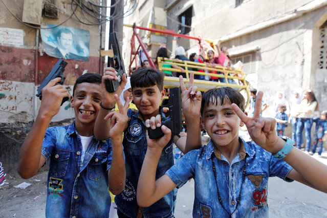 Boys pose with their toy guns as others play on swings, on the first day of the Muslim holiday of Eid al-Fitr, which marks the end of the holy month of Ramadan, in the government-controlled district of Dwelaa in Damascus, Syria July 6, 2016. (Photo by Omar Sanadiki/Reuters)