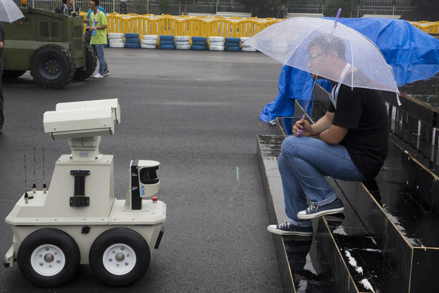 A worker waits for the rain to stop near an autonomous vehicle a day before the opening of the World Robot Conference held in Beijing, China, Tuesday, August 22, 2017. (Photo by Ng Han Guan/AP Photo)