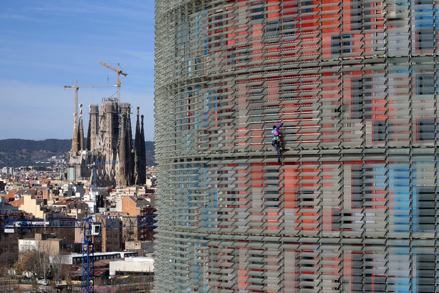 French urban climber, Alain Robert, right, scales the 144 meters (472 ft) of the Glories tower with the La Sagrada Familia Basilica designed by architect Antoni Gaudi in the background, left, in Barcelona, Spain, Wednesday, March 4, 2020. Robert, known as Spiderman climbed up 144 meters of the Glories tower, previously known the Agbar tower in around 20 minutes. Spanish authorities briefly detained him after the stunt. (Photo by Joan Mateu/AP Photo)