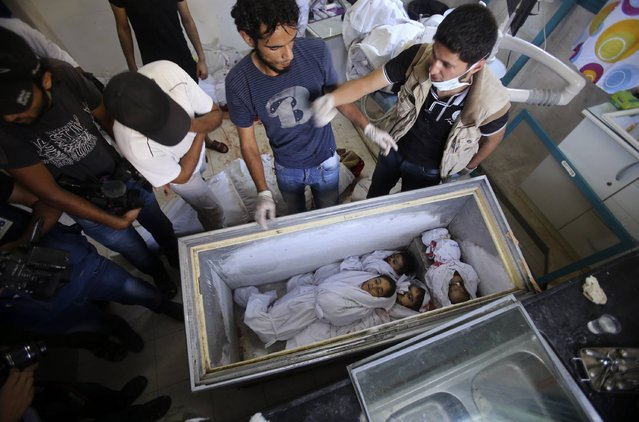 Picture taken on August 3, 2014, at the morgue in Rafah in the southern Gaza Strip shows the bodies of a baby and children lying in an ice-cream freezer, who died along with other members of al-Ghul and Abu Jazar families after their houses were hit by an Israeli military strike. At least 10 people died as well in a fresh strike on a UN school in Gaza shortly after Israel confirmed it had begun withdrawing some troops from the war-torn enclave. (Photo by Abed Rahim Khatib/NurPhoto)