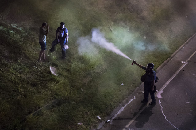 An officer releases pepper spray on demonstrators blocking I-94 near the Dale St. exit during a protest for Philando Castile in Falcon Heights, Minn. on Saturday July 09, 2016. Philando Castile was shot and killed after a traffic stop by police in Falcon Heights, Wednesday night. A video shot by Diamond Reynolds of the shooting went viral. (Photo by Jabin Botsford/The Washington Post)