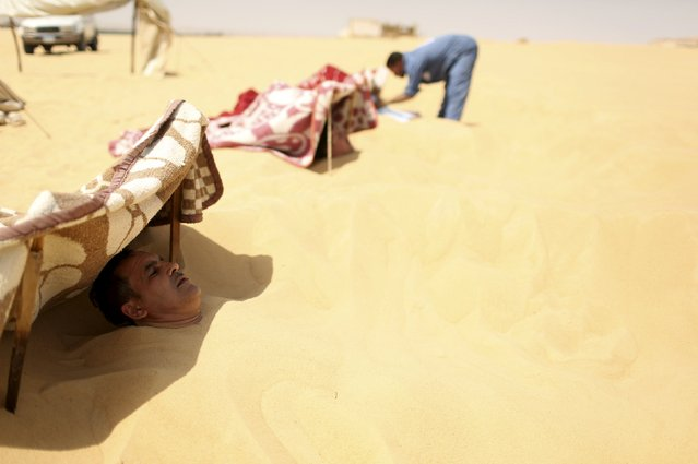 A woker tends to patients buried in the sand in Siwa, Egypt, August 11, 2015. (Photo by Asmaa Waguih/Reuters)