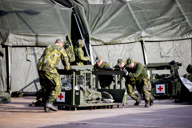 Military personnel work at a military field hospital, as the spread of coronavirus disease (COVID-19) continues, at the Ostra Sjukhuset hospital area in Gothenburg, Sweden, March 23, 2020. (Photo by Adam Ihse/TT News Agency via Reuters)