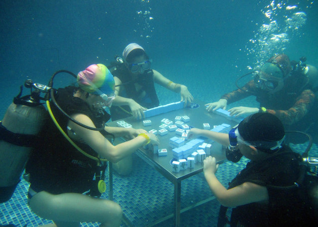 Divers play mahjong in a swimming pool during a hot summer day in Chongqing, China, July 17, 2016. (Photo by Reuters/Stringer)