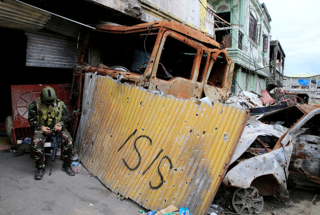 A government soldier checks his mobile phone in front of damaged houses and buildings as troops continue their assault on clearing operations against the pro-IS militant group which seized Mapandi district in Marawi city, southern Philippines, September 13, 2017. (Photo by Romeo Ranoco/Reuters)