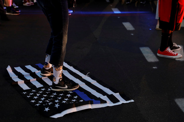 """A protester stands on a """"Blue Lives Matter"""" flag after the not guilty verdict in the murder trial of Jason Stockley, a former St. Louis police officer, charged with the 2011 shooting of Anthony Lamar Smith, who was black, in St. Louis, Missouri, U.S., September 15, 2017. (Photo by Whitney Curtis/Reuters)"""