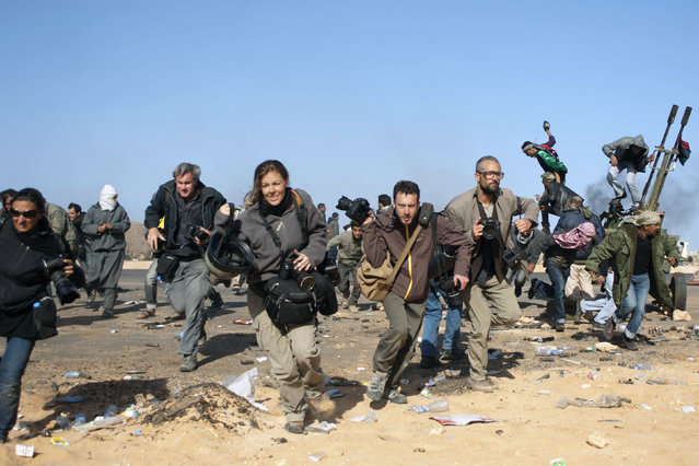 Journalists, including New York Times photographers Tyler Hicks (R- in glasses) and Lynsey Addario (far L), Getty Images photographer John Moore (2nd L), freelance photographer Holly Pickett (3rdL) and freelancer Philip Poupin (4th L) run for cover during a bombing run by Libyan government planes at a checkpoint near the oil refinery of Ras Lanuf March 11, 2011. (Photo by Paul Conroy/Reuters)