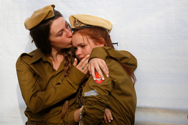 """Israeli soldiers cry during a state memorial ceremony marking two years since the  2014 Gaza war """"Operation Protective Edge"""" at Mount Herzl military cemetery in  in Jerusalem, Israel, 26 July 2016. More than 2.000 people were killed in the conflicts between Israel and Palestine. (Photo by Abir Sultan/EPA)"""