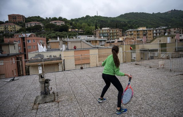 Vittoria Oliveri (front) plays tennis with Carola in background on rooftops of their house in Finale Ligure, Liguria Region, northwestern Italy on April 19, 2020, during the country's lockdown aimed at stopping the spread of the COVID-19 (new coronavirus) pandemic. Everyday Carola, 11, and Vittoria, 13, play tennis from a rooftop to another rooftop of their homes to practice during the Covid 19 lockdown. (Photo by Marco Bertorello/AFP Photo)