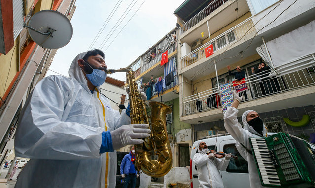 "Members of a new music band named ""Evde Kal"" (Stay at home) wearing medical suits, face masks and gloves perform in the streets of the city for the people staying inside as a precaution against the coronavirus (COVID-19) pandemic in Izmir, Turkey on April 05, 2020. (Photo by Mehmet Emin Menguarslan/Anadolu Agency via Getty Images)"