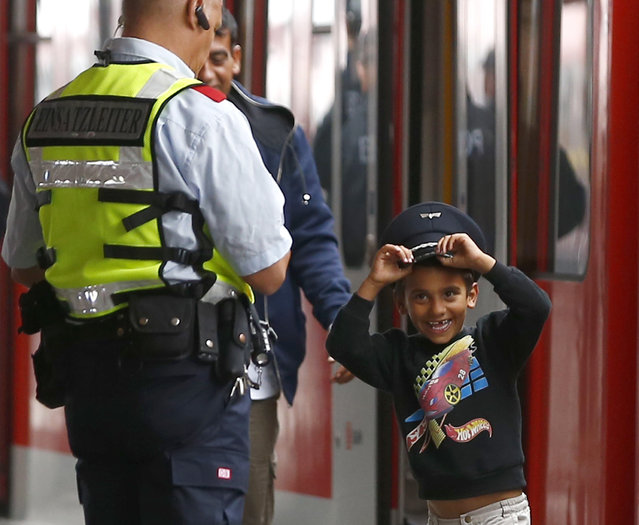 """A young migrant boy tries on a Bahn security officer's cap after arriving with the first """"special"""" train from Salzberg, before boarding a regional S-Bahn train, at the main station in Munich, Germany September 5, 2015. (Photo by Michael Dalder/Reuters)"""